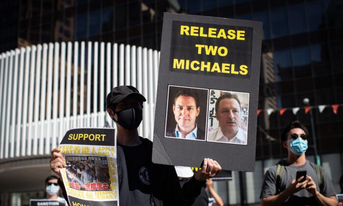 Человек держит табличку с фотографиями Майкла Коврига и Майкла Спавора, задержанных в Китае с декабря 2018 года. Митинг в поддержку демократии в Гонконге, Ванкувер, Британская Колумбия. 16 августа 2020 года.