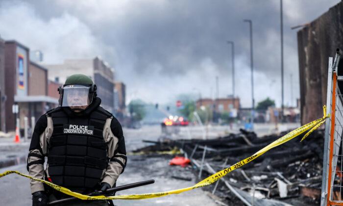 Полицейский стоит среди дыма и обломков на фоне горящего здания после ночи протестов и насилия после смерти Джорджа Флойда в Миннеаполисе, штат Миннесота, 29 мая 2020 года