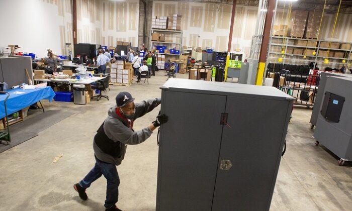 Сотрудник округа Фултон перемещает машины для голосования на хранение в Центр подготовки к выборам округа Фултон в Атланте, 4 ноября 2020 года.