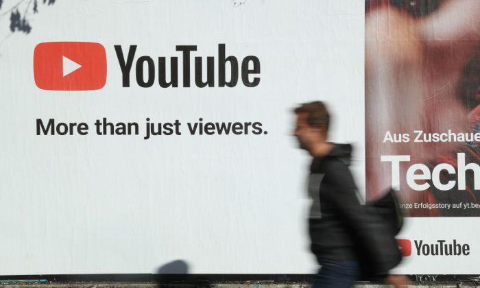 Мужчина проходит мимо рекламного щита YouTube в Берлине 5 октября 2018 года