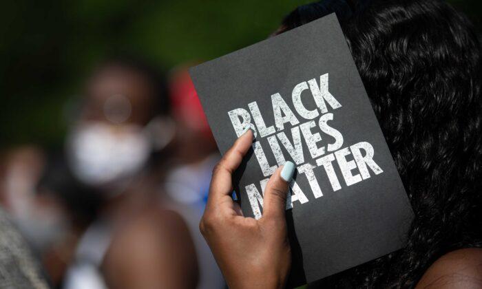 Демонстрант держит карточку с надписью «Black Lives Matter» у здания суда округа Глинн в Брансуике, штат Джорджия, 4 июня 2020 года