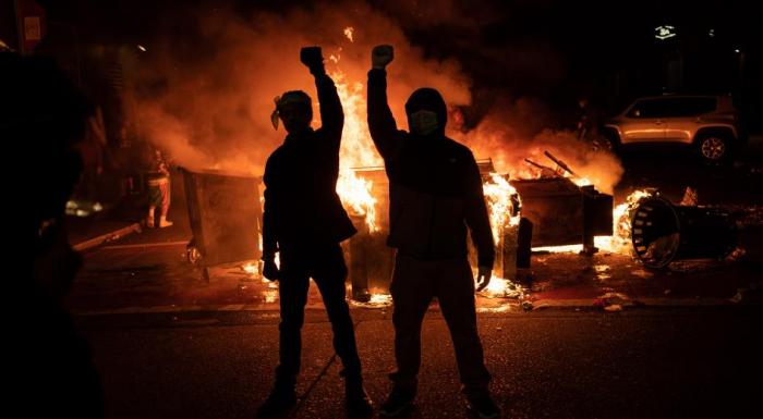Демонстранты поднимают кулаки во время пожара на улице после столкновений с правоохранительными органами возле полицейского управления Сиэтла, 8 июня 2020 года