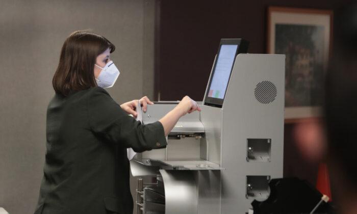 Работник избирательной комиссии собирает результаты подсчёта бюллетеней, отправленных по почте, в машине для голосования в Милуоки, штат Висконсин, 4 ноября 2020 года