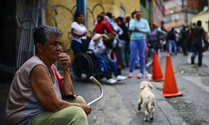 Пожилая женщина ждёт в очереди, чтобы купить основные продукты питания и предметы домашнего обихода у супермаркета в бедном районе Лидице, в Каракасе, Венесуэла, 27 мая 2016 года
