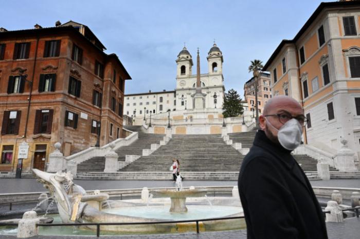 Мужчина в маске стоит перед заброшенной Испанской лестницей в Риме 12 марта 2020 года