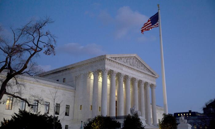Американский флаг развевается перед зданием Верховного суда США в Вашингтоне, 13 февраля 2016 года
