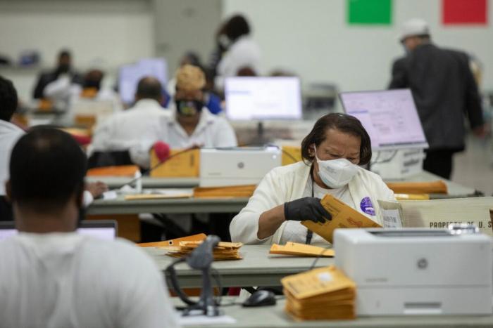 Сотрудники избирательной комиссии обрабатывают бюллетени, отправленные по почте