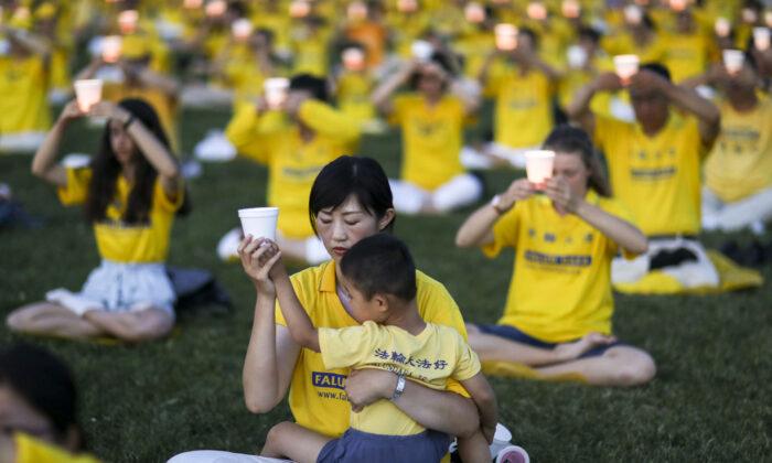 Практикующие Фалуньгун во время ежегодного бдения при свечах, посвященного 20-летию начала преследования Фалуньгун в Китае, на западной лужайке Капитолийского холма, 18 июля 2019 года