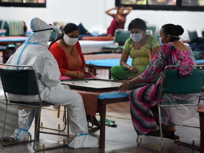 Пациенты играют в карром в Центре ухода за больными с COVID-19 в спортивном комплексе CWG Village в Нью-Дели
