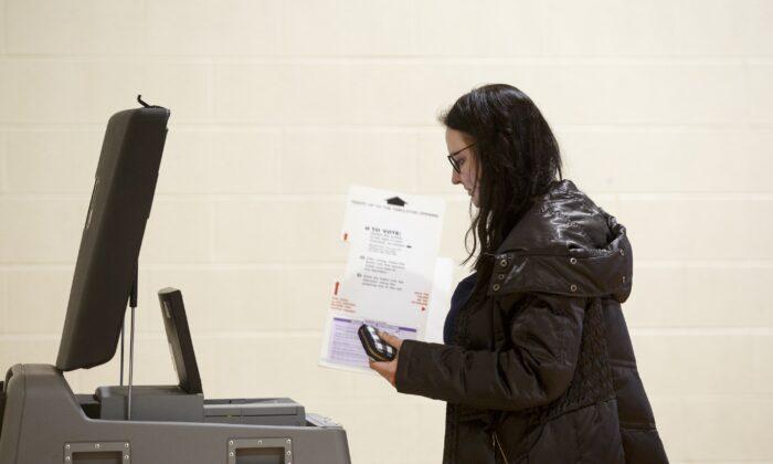 Избиратель из Мичигана использует машину для голосования во время президентских первичных выборов в Уоррене, штат Мичиган. 10 марта 2020 года