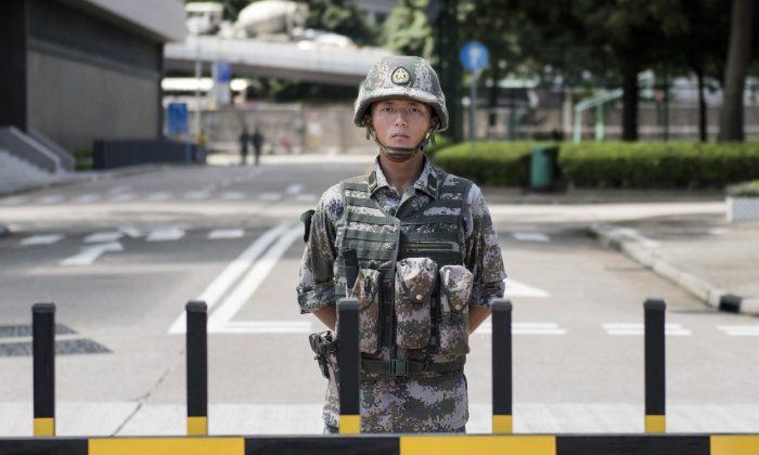 Солдат НОАК стоит на страже у входа в штаб-квартиру гарнизона НОАК в Гонконге, 29 августа 2014 года