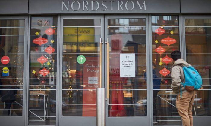 Мужчина стоит перед закрытым магазином Nordstrom в центре Торонто, Канада, 23 ноября 2020 года