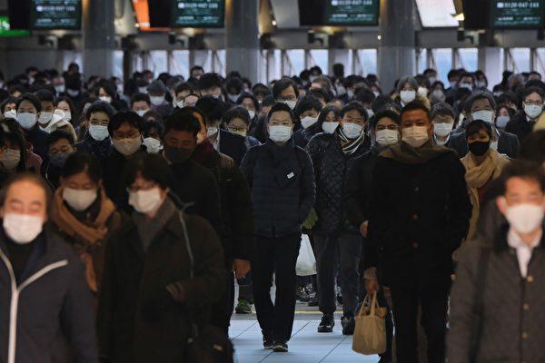 Пассажиры в масках идут через станцию Синагава в Токио, 8 января 2021 года
