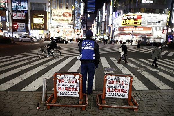 Полицейский просит людей воздерживаться от выходов после 20:00 в районе Синдзюку в Токио 8 января 2021 года в первый день действия чрезвычайного положения из-за пандемии коронавируса