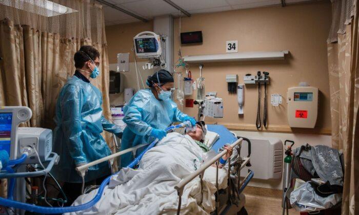 Медицинские работники используют аппарат ИВЛ для пациента с COVID-19, который испытывал затруднения с дыханием, в Медицинском центре «Провиденс-Сент-Мэри», Калифорния, 11 января 2021 года