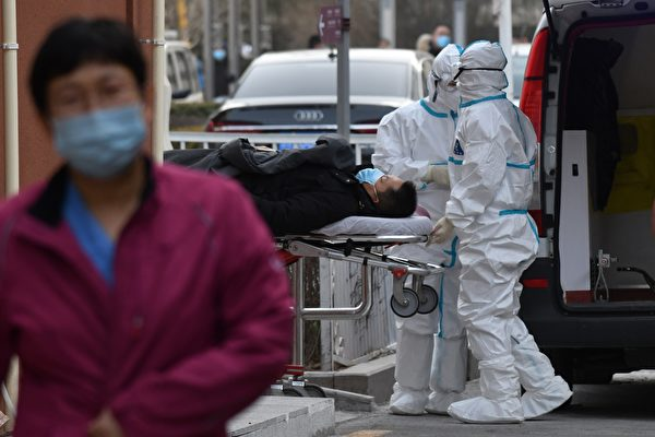 Медицинские работники в защитных костюмах в качестве меры предосторожности против COVID-19 доставляют пациента в больницу, Пекин, 13 января 2021 года