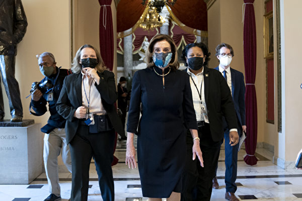 Спикер палаты представителей Нэнси Пелоси в защитной маске входит в вестибюль Палаты представителей в Капитолии США, Вашингтон, округ Колумбия, 13 января 2021 года