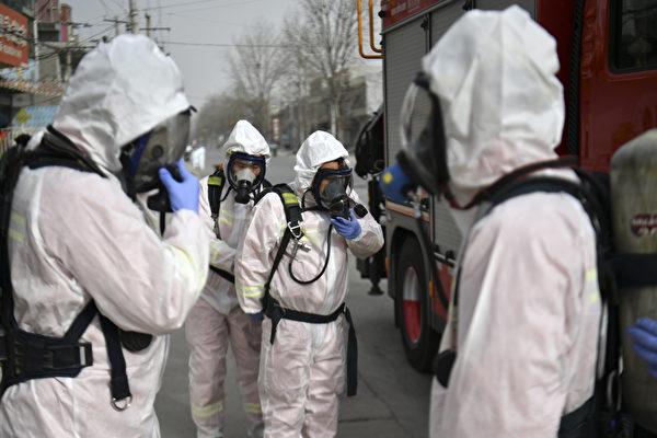 Люди в защитных костюмах готовятся распылить дезинфицирующее средство на улице в районе Гаочэн, который был объявлен зоной высокого риска в Шицзячжуане, в провинции Хэбэй на севере Китая, 15 января 2021 года