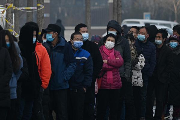 Люди выстраиваются в очередь для проверки на коронавирус Covid-19 в районе Дасин в Пекине, 26 января 2021 года