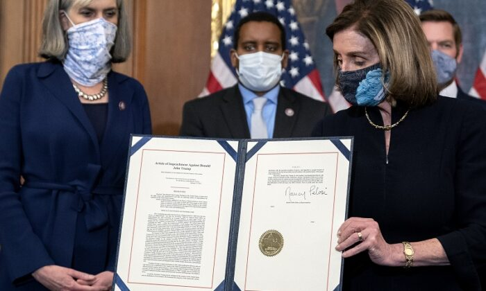 Спикер палаты представителей США Нэнси Пелоси показывает подписанную статью об импичменте президенту США Дональду Трампу в Капитолии США, Вашингтон, 13 января 2021 года