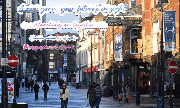 Пешеходы идут по пустой торговой улице в Лидсе, на севере Англии, 6 января 2021 года, во второй день национального карантина для борьбы с распространением COVID-19