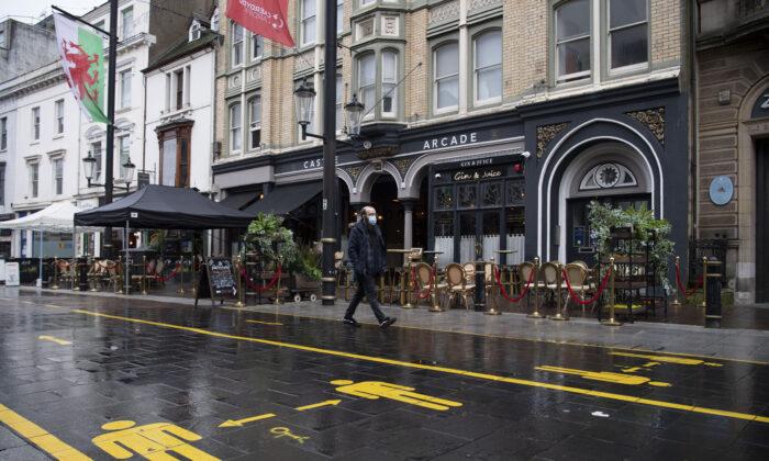 Мужчина в маске проходит мимо пустых баров в Кардиффе, Уэльс, 23 октября 2020 года