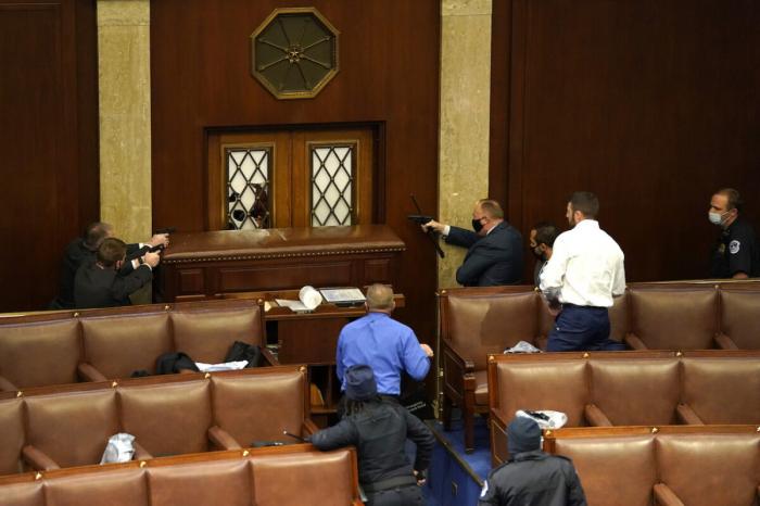 Сотрудники правоохранительных органов направляют оружие на дверь в зале Палаты представителей во время совместного заседания Конгресса в Вашингтоне, 6 января 2021 года