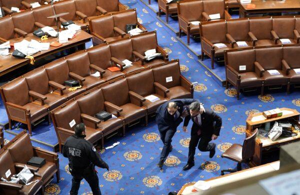 Члены Конгресса бегут в поисках укрытия, поскольку группа протестующих пытается войти в зал Палаты представителей во время совместного заседания Конгресса в Вашингтоне, 6 января 2021 года