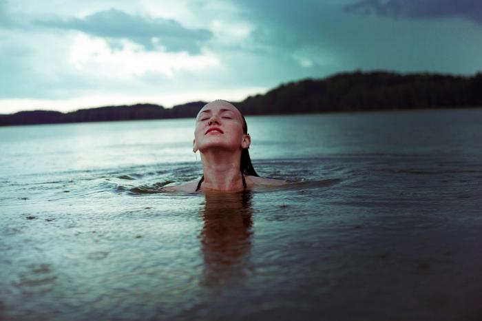 Девушка плавает в реке.