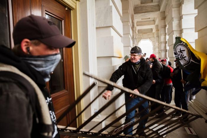 Протестующие громят вход в здание Капитолия в Вашингтоне, 6 января 2021 года