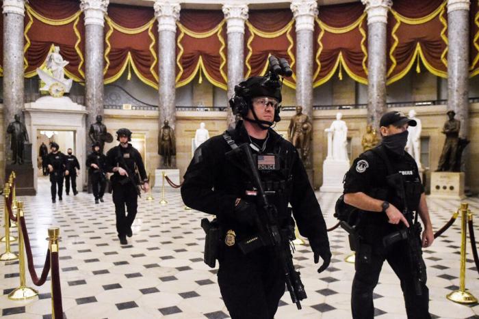 Группа спецназа патрулирует Национальный скульптурный зал, прежде чем вице-президент Майк Пенс войдет в зал Капитолия США в Вашингтоне, 7 января 2021 года