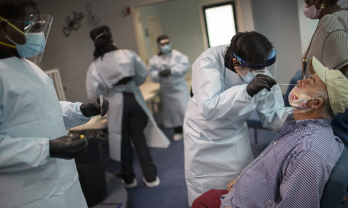 Медицинский работник берёт мазок из носа, чтобы проверить пациента на COVID-19, Пемброк-Парк, штат Флорида, 22 июля 2020 года