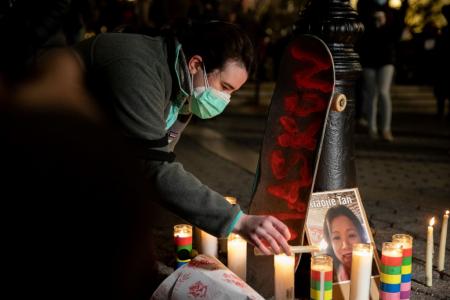 Человек зажигает свечи во время бдения по жертвам антиазиатских преступлений на почве ненависти на Юнион-сквер в Нью-Йорке 19 марта 2021 года.