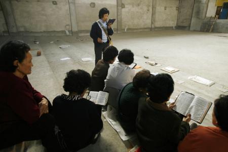 Этнические корейские христиане поют гимны в своей недостроенной церкви в городе Яньцзи в Корейской автономной префектуре Яньбянь на границе Китая и Северной Кореи 13 октября 2006 года.