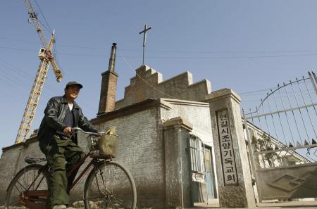Мужчина проезжает на велосипеде мимо этнической корейской христианской церкви в городе Яньцзи в Корейской автономной префектуре Яньбянь на границе Китая и Северной Кореи, 13 октября 2006 года.