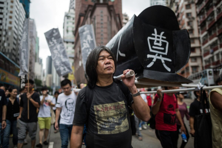 Леунг Квок-хунг, известный как «Длинноволосый», помогает поддерживать макет гроба, когда он посещает митинг в Гонконге 31 мая 2015 года, чтобы отметить подавление протестующих 1989 года на площади Тяньаньмэнь в Пекине, перед 26-й годовщиной инцидента 4 июня.