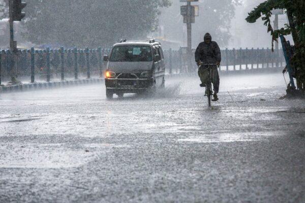 Мужчина во время проливного дождя из-за циклона «Яас» в Калькутте, Индия, 26 мая 2021 года.
