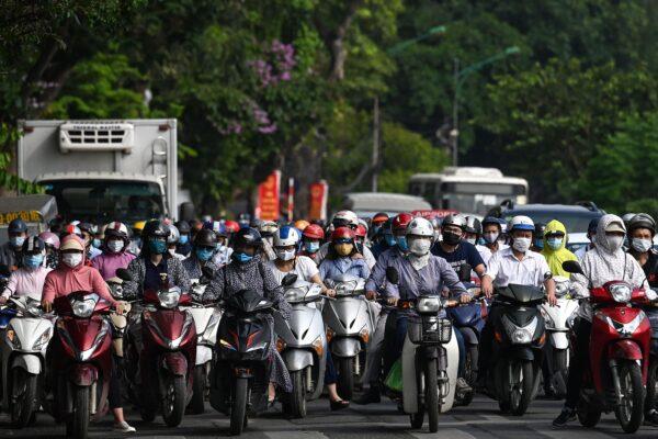 Водители в масках ждут на светофоре в Ханое, Вьетнам, 4 мая 2021 года.