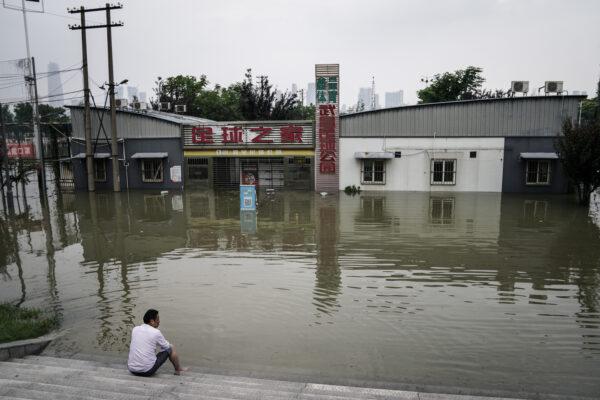 Житель сидит у затопленного парка Цзянтань около реки Янцзы в Ухане, Китай, 10 июля 2020 г.