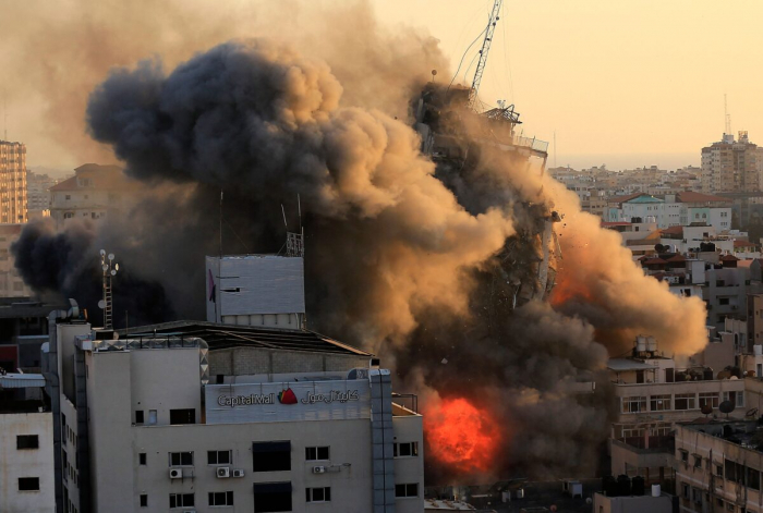 Сильный дым и огонь окружают башню Аль-Шарук, которая рухнула после израильского авиаудара в городе Газа 12 мая 2021 г.