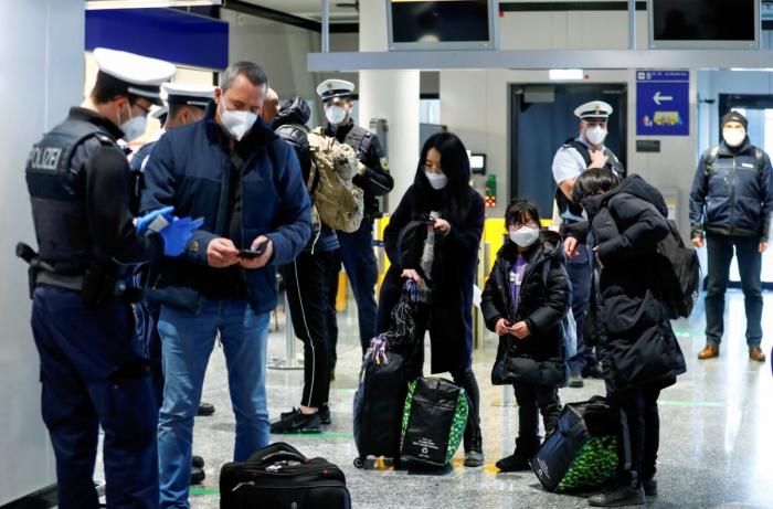 Сотрудники федеральной полиции проверяют авиапассажиров, прибывающих из Великобритании в аэропорт Франкфурта, поскольку распространение COVID-19 продолжается. Франкфурт, Германия, 30 января 2021 года.