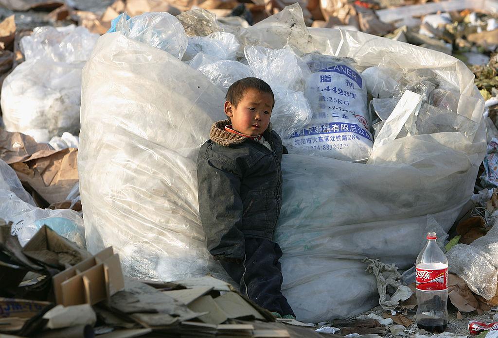 Китайский ребёнок рабочих-мигрантов играет насвалке окраины Пекина, Китай