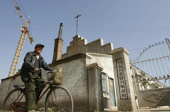 Мужчина проезжает мимо этнической корейской христианской церкви в городе Яньцзи Корейского автономного округа Яньбян на границе Китая и Северной Кореи в Яньцзи, Китай, 13 октября 2006 г.