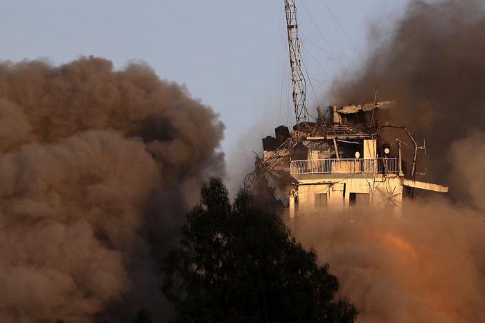 Сильный дым и огонь поднимаются над башней Аль-Шарук после израильского авиаудара в городе Газа 12 мая 2021 года.