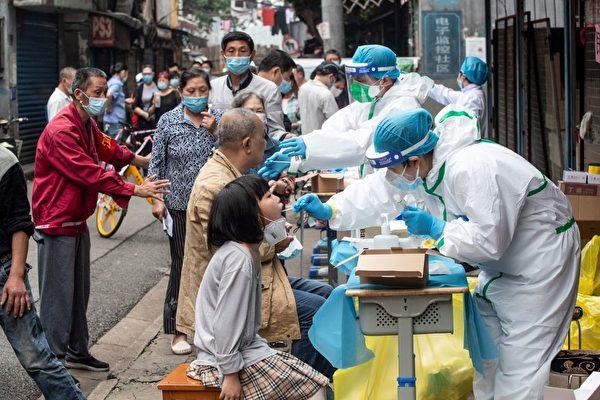 Медицинские работники берут образцы ужителей, чтобы проверить ихнаCOVID-19 наулице вУхане, провинция Хубэй, Китай, 15мая 2020 года.