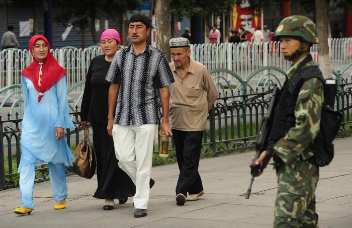 Китайский полицейский наблюдает засемьёй уйгуров.