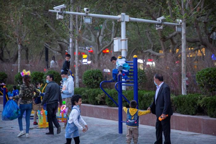 Дети играют на детской площадке возле камер видеонаблюдения в Аксу, Синьцзян-Уйгурский автономный район, Китай, 20 апреля 2021 г.