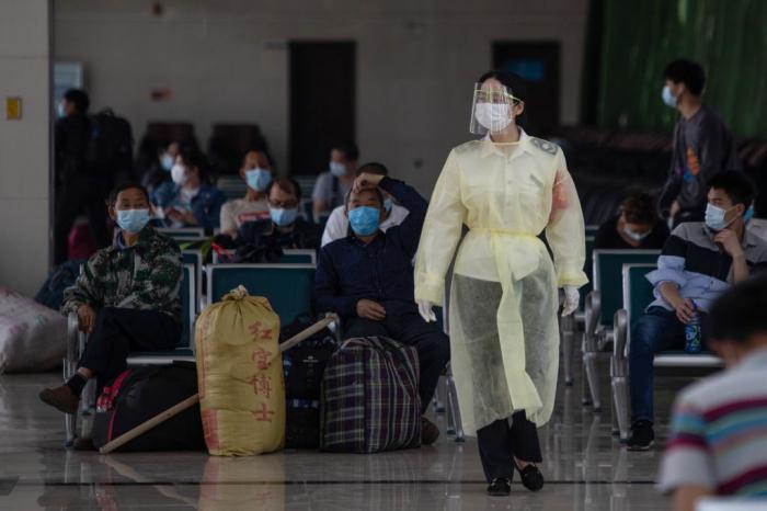 Сотрудница полиции в защитной маске идёт по залу автобусной станции в Ухане, центральная китайская провинция Хубэй, 30 апреля 2020 года.