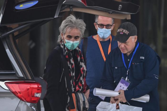 Члены группы ВОЗ: британский зоолог Питер Дасзак (справа) и нидерландский вирусолог Марион Купманс (слева) в сопровождении главы миссии ВОЗ Питера Бена Эмбарека (в центре) покидают отель в городе Ухане провинции Хубэй в центральном Китае, 10 февраля 2021 г.