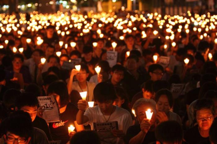 Люди собрались в парке Виктория в Гонконге 4 июня 2011 года по случаю 22-й годовщины кровавого подавления демократических демонстраций на площади Тяньаньмэнь